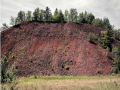 Photo of a large dirt hill with trees on top